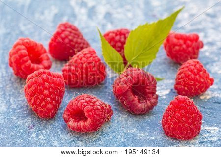 Raspberries on blue stone background. natural fruits