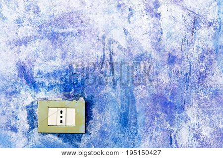 Blue painted wall with an electrical outlet.