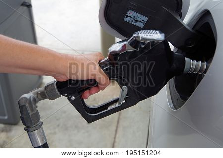 Hand holding gas pump inserted in gas tank of car