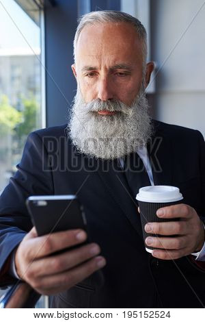 Vertical of sad sir age of 50-60 holding cup of coffee and surfing in phone