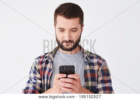 Close-up shot of casual bearded man standing against white background while holding mobile phone and sending email