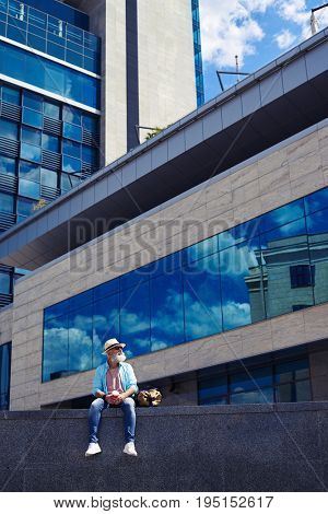 Vertical of nice sir in hat enjoying city while drinking coffee and sitting under skyscraper with copy space