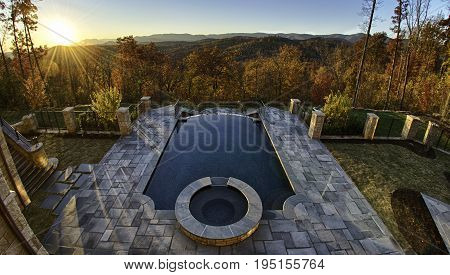 Luxurious Pool Overlooking beautiful Autumn Fall Hillside with orange, brown and green leaves falling from trees and golden sunlight pouring in