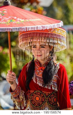 CHIANGMAI THAILAND - JANUARY 25 2015: Hill Tribe girl holding local paper umbrella in parade of 22nd Traditional Skirt Fabric and The Indigenous Product and Culture Festival in Mae Chaem Chiangmai Thailand