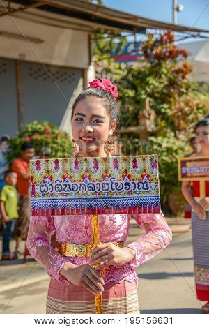 Chiangmai Thailand - January 25 2015: Indigenous girl with local traditional costume holding board of fabric design name in parade of 22nd Traditional Skirt Fabric and The Indigenous Product and Culture Festival in Mae Chaem Chiangmai Thailand