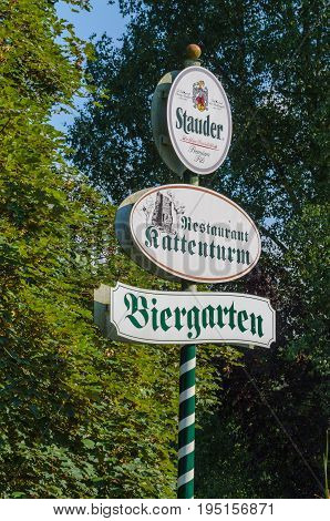 ESSEN NRW GERMANY - JULY 23 2014: Advertising Sign in Essen district of Kettwig near the restaurant at the Kattenturm. Green and white striped wooden post with advertising surface.