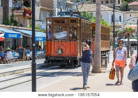 PORT DE SOLLER SPAIN - JUNE 02 2016:Vintage train tram on the beach promenade of the town of Soller in Spain. Opened in 1913 the driving distance is about 5 km long.