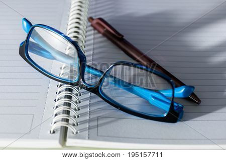 Close up a pen,  blue old glasses and notepad