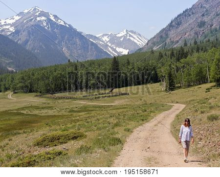 LAKE CITY, COLORADO, JUNE 20. The Alpine Loop Backcountry Byway on June 20, 2017, near Lake City, Colorado. A Woman Walks a Dirt Road on the Alpine Loop Backcountry Byway in Colorado.