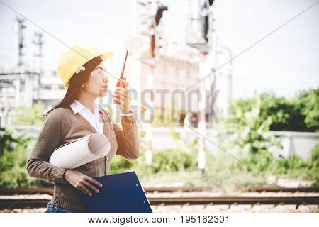 Engineers woman holding radio blueprint and report schedule for workers security control at power plant energy industry. Engineer Concept