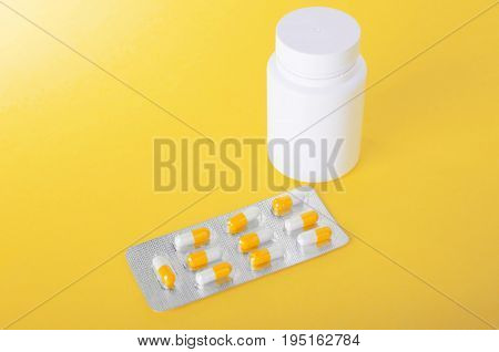 Painkillers in a gray package on a spacious and bright yellow background. Pills, painkillers, drugs, vitamins, tablets in capsules. Packaging for drugs: antibiotics, vitamins and aspirin tablets.
