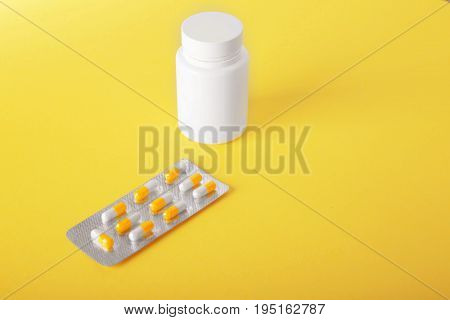 Packaging of orange and white tablets and capsules with medicine bottle on a yellow background. Antibiotics, painkillers as medical treatment. Tablets of the drug for treatment. Medicinal drugs.