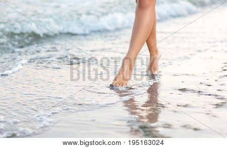 Beautiful, long and smooth woman's legs go along the sand near the sea. Sexy woman's legs. Adorable long-legged girl walks near the sea on the sand.