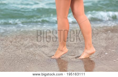 Pretty female legs on the background of the sea. A Charming long-legged girl walks near the sea on the sand. A girl with beautiful legs walks along the sea. Beautiful, long and smooth woman's legs.