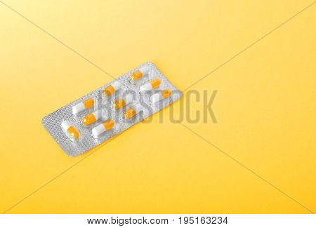 Pills, painkillers, drugs, vitamins, tablets in capsules. Close-up various colorful prescripted drugs. Orange and white aspirin in blisters. Pharmaceutical supplement. Medical vitamins.