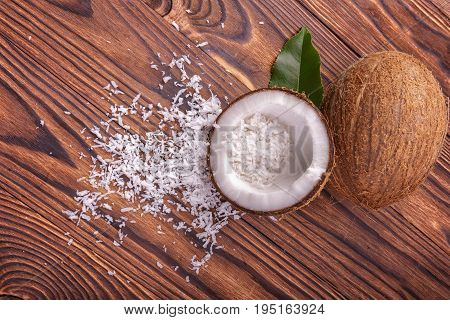 Close-up two fresh coconuts on a brown wooden background. Delicious healthful cut coco with a dark green leaf. White coconut flakes on a wooden table.