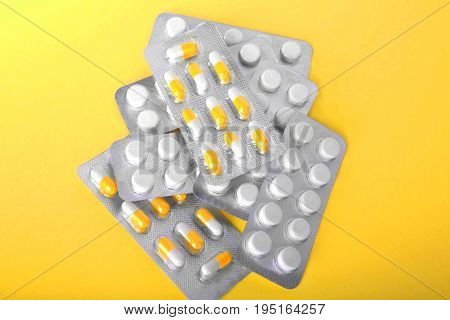 Pills, tablets, and antibiotics on a bright yellow background. Various packagings of orange and white tablets and capsules. Close-up various colorful prescripted drugs. Pills as medical treatment.