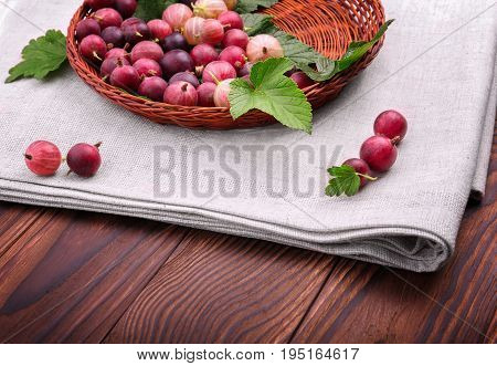 Close-up fresh gooseberries on a white fabric on a dark brown wooden table. An eco-friendly wooden basket with nutritious gooseberries on a brown table. A great basket full of delicious gooseberries.