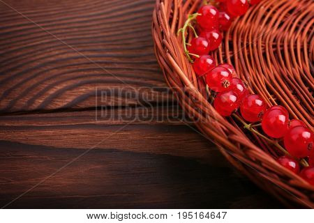 A colorful partial composition of a brown basket with juicy red currant on a dark brown wooden table. Mature, juicy, raw, fresh, tasty, healthy, nutritious concept. Delicious bright red currant.