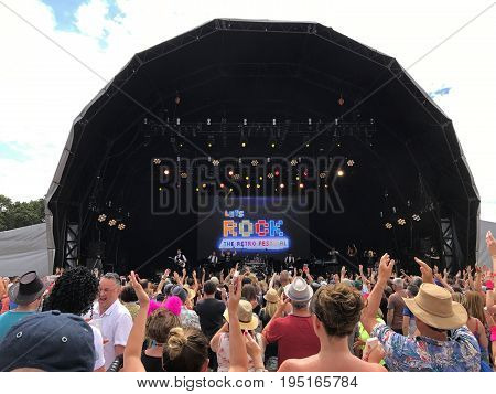 SOUTHAMPTON UK - July 8 2017: Lets Rock Southampton 80s music festival in Southampton UK on a cloudy day with some blue sky. Stage wtih fans dancing and having fun.
