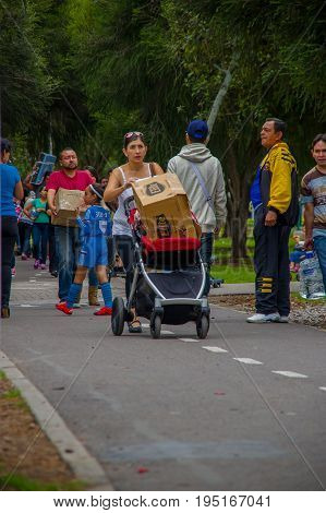 Quito, Ecuador - April, 17, 2016: Unidentified people with a paperboard box with food inside, providing disaster relief food, clothes, medicine and water for earthquake survivors in the coast.