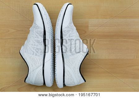 Top view side of white casual shoes with black lines on wooden background
