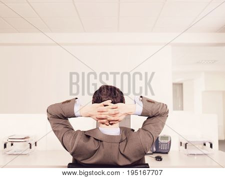 Rear view of a male office worker relaxing at desk
