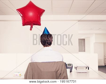 Rear view of a man in party hat by red balloon working alone in office