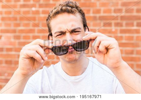 Funny man with sunglasses portrait wall on background. Young man holding sunglasses and looking at camera. Cheerful caucasian man wearing white t-shirt