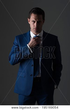 Successful Man Adjusting Tie In Stylish Blue Formal Suit