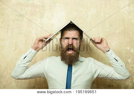man. hipster with long beard and stylish hair on shouting face in tie and white shirt hold laptop on textured beige background digital marketing and business agile business businessman