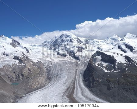 Monte Rosa, landscape of alpine glacier and Dufourspitze highest mount in swiss Alps at SWITZERLAND, from Gornergrat near Zermatt village, cloudy blue sky in 2017 warm sunny summer day, Europe on July