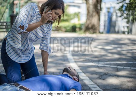 girl calling emergency service to assist a guy with cpr