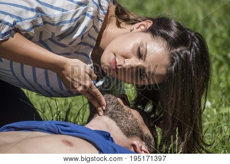 girl making cardiopulmonary resuscitation to an unconscious guy after heart attack poster