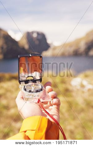 Closeup of a hiker holding out compass over blurred mountain landscape