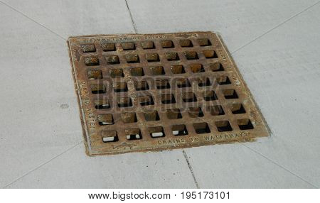 Rusty metal, square drainage cover on concrete surface.