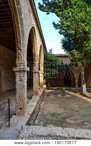 Several stone arches receding into the distance in the courtyard of an old castle