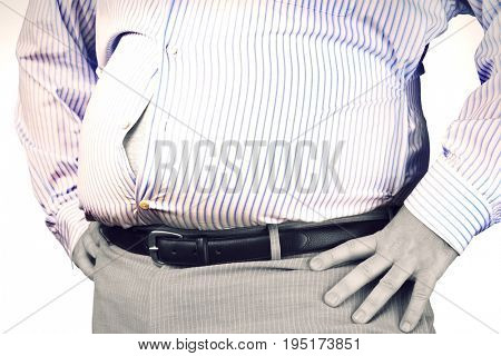 Closeup midsection of an overweight man standing with unbuttoned shirt and hands on hip