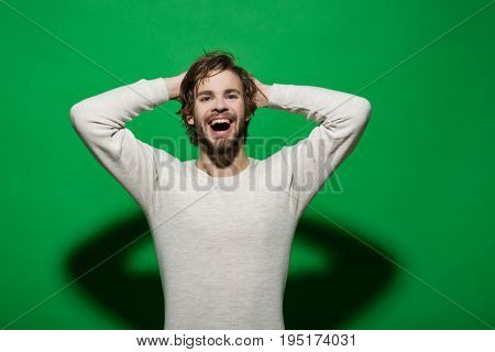 handsome man smiling with beard and stylish hair in white underwear with pointing fingers on red background morning and fashion product presentation