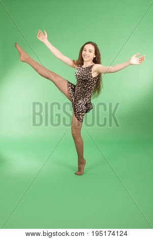 Beautiful girl dancing in trendy pantera dress and raised her leg up. Isolated on green