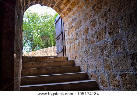 Stone steps lead up to the arched entrance of the basement