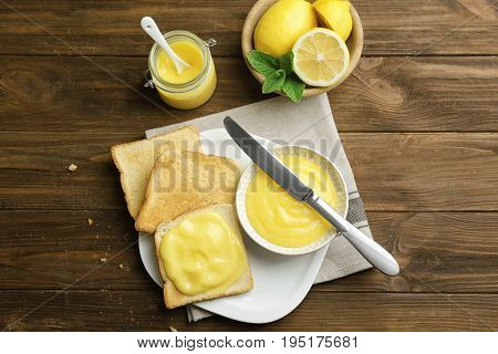 Composition with fresh toasts and delicious lemon curd on wooden table