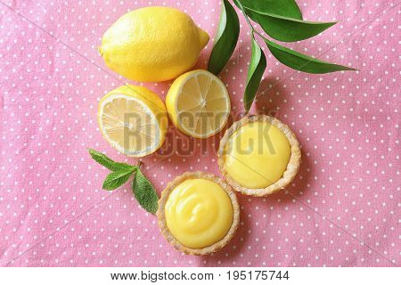 Tasty cookies with lemon curd on table