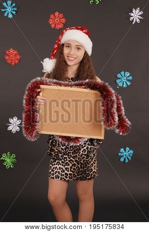 Young christmas girl in santa hat with blank cork board on black background