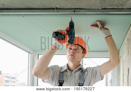 Worker is fixing the drywall to the ceiling with screwdriver.