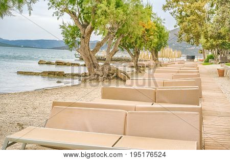 Picturesque beach with sun beds on the shore of the Mirabello Bay on the island of Crete Greece