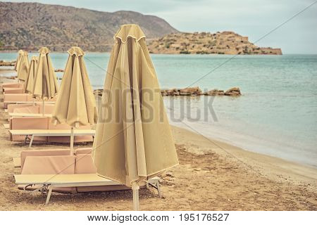 Deserted beach with sun umbrellas and sun beds on a cloudy summer day. Greece island Crete. Photo toned