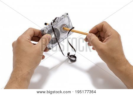 Spinning tape cassette by pencil isolated on white background.