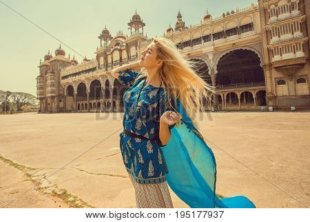 Romantic happy girl with blue headscarf walk past famous building with arches of the royal Palace of Mysore. Karnataka state, India