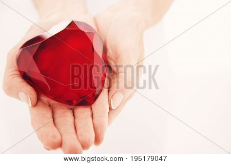 Closeup midsection of a woman holding heart shaped jewel